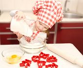 Little Girl With Chef Hat Put Flour For Baking Cookies