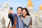 Lovers - young couple happy taking selfie photo with smart phone camera. Modern urban city man and w