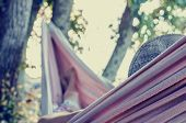 stock photo of rest-in-peace  - Vintage toned image with an instagram effect of a woman relaxing on a hot summer day in a hammock strung in the shade of a tree - JPG
