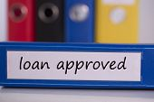 The word loan approved on blue business binder