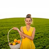 Young Woman With Basket Full Of Fruits Smiling On Greenfield Of Grass In Yellow Dress With Place For