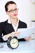 Business woman is working in office and holding some documents. Clock in front, deadline concept.