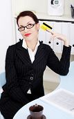 Business woman is holding credit card, in office.