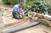 Man installing gravel path in garden