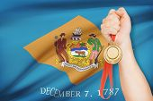 Medal In Hand With Flag On Background - State Of Delaware