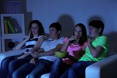 Group of young friends watching television at home of blacking-out
