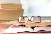 Composition with glasses and books, on table, on light background