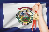 Medal In Hand With Flag On Background - State Of West Virginia. Part Of A Series.