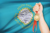 Medal In Hand With Flag On Background - State Of South Dakota. Part Of A Series.
