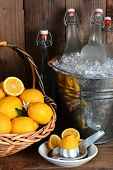 Bottles of fresh squeezed lemonade in a metal bucket filled with ice. A basket of lemons and a juicer fill out the rustic still life. Vertical format.