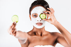 picture of mud pack  - Young African woman in Studio doing body care with refreshing cucumber facial mask for young and beautiful skin and relaxation - JPG