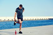 Muscular male athlete doing workout in beautiful sea port