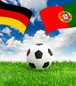 Soccer Ball On Green Grass And Flags Of Germany And Portugal
