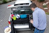 Dad Preparing Car Trunk For Holiday