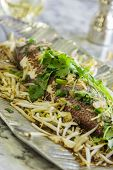 stock photo of bean sprouts  - Hawaiian pink snapper boiled and served with warm soy sauce and sesame oil and topped with ginger garlic green onions bean sprouts and cilantro - JPG