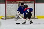 stock photo of shoot out  - Young ice hockey player prepares to shoot on net - JPG