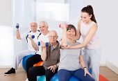 Trainer Assisting Senior People At Healthclub