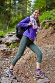 Woman With Backpack Hiking Into The Forest
