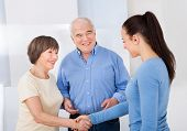 Caregiver Shaking Hands With Senior Couple