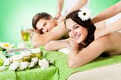 Smiling Couple Receiving Shoulder Massage At Beauty Spa