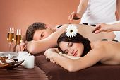 Relaxed Couple Receiving Hot Stone Therapy At Spa