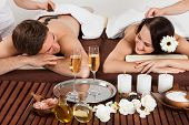 Couple Enjoying Hot Stone Massage At Spa