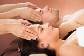 Relaxed Couple Receiving Head Massage At Spa