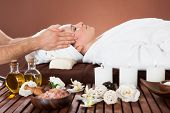 Relaxed Woman Receiving Head Massage At Spa