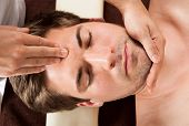 Young Man Receiving Forehead Massage In Spa