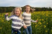 happy kids  sisters running around laughing  in the meadow