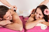 Couple Enjoying Hot Stone Massage At Beauty Spa