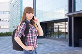 Teenage Girl With Cell Phone Standing On Street Against School Building