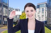 Beautiful Business Woman Showing Visiting Card On Street Against Modern Office Building