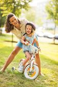 Portrait Of Mother And Baby Girl With Bicycle
