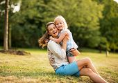 Portrait Of Happy Mother And Baby Girl Hugging In Park