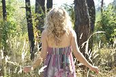 In The Autumn Forest On A Glade Curly Girl In Tall Grass In The Spikelets.