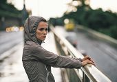 Portrait Of Fitness Young Woman Looking Into Distance In Rainy C