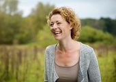 foto of close-up middle-aged woman  - Close up portrait of a smiling middle aged woman outdoors - JPG