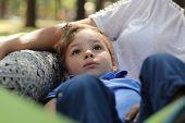 Boy Resting On Mother Leg