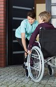 Caregiver Helping Disabled Woman Entering Home