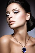 Beautiful brunette with a bright evening make-up with a necklace Heart of the Ocean.