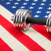 Dumbbell Weights Over Usa Flag As Symbol Of Healthy Nation