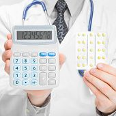 Doctor Holdling Calculator And Pills In His Hands - Heath Care Concept