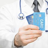 Doctor Holding Two Credit Cards In His Hand - Closeup Studio Shot