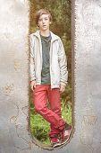 stock photo of metal sculpture  - teenager boy standing in a huge metal letter - JPG