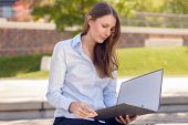 Attractive Woman Reading A Business File In A Park