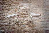 Two  Observation Cameras On A Ancient Natural Stone Wall