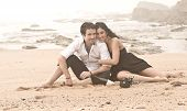 Young beautiful couple sitting together on beach