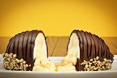 Chocolate coated bananas cake with nuts yellow background