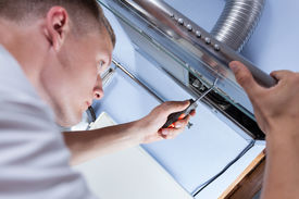 foto of handyman  - Young handyman fixing a kitchen extractor with a screwdriver - JPG